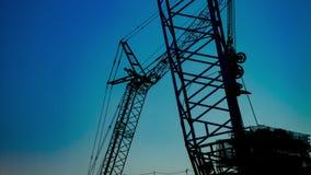 Un laps de temps des grues mobiles derrière le ciel bleu au crépuscule en construction banque de vidéos