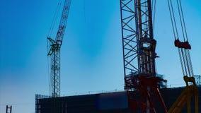 Un laps de temps des grues mobiles derrière le ciel bleu au crépuscule en construction clips vidéos
