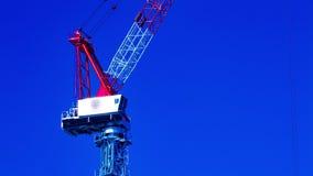 Un lapso de tiempo de grúas móviles detrás del cielo azul en la inclinación inferior del primer de la construcción almacen de video