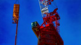 Un lapso de tiempo de grúas móviles en la construcción inferior en la inclinación del primer de Tokio metrajes