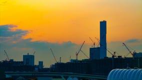Un lapso de tiempo de grúas móviles en la construcción inferior en Tokio en la inclinación tirada amplia de la oscuridad almacen de metraje de vídeo