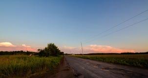 Un lapso de tiempo de una carretera nacional rural entre los campos en la puesta del sol almacen de metraje de vídeo