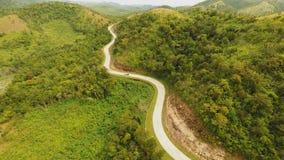 Un largo y una carretera con curvas que pasan a través de las colinas verdes Isla de Busuanga Coron Silueta del hombre de negocio metrajes