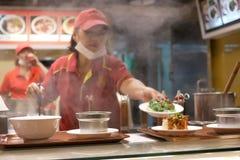 Un lato del cuoco unico che cucina alimento per il cliente con vapore pesante fotografia stock