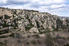 Un lato della collina coperto di camini leggiadramente vicino al museo dell'aria aperta in Goreme nella regione di Cappadocia di  Fotografia Stock