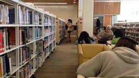 Un lato della gente che gode che legge dentro la biblioteca video d archivio