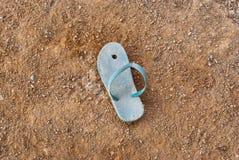 Un lato della pantofola consumata di piccola dimensione blu abbandonata su terra Immagine Stock