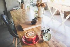 Un latte della tazza di caffè con la sveglia ed il manuale sulla tavola dentro Fotografia Stock