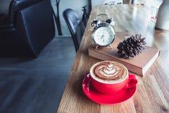Un latte della tazza di caffè con la sveglia ed il manuale sulla tavola dentro Fotografia Stock Libera da Diritti