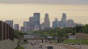 Un lavado de la luz anaranjada de la tarde sobre el horizonte distante de Minneapolis y del tráfico de la carretera en el primero almacen de metraje de vídeo