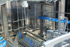 Un lavaplatos para los platos y los cubiertos ahorra tiempo y el dinero y el lavaplatos ahora es un placer y no una obligación Imágenes de archivo libres de regalías