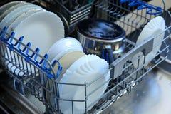 Un lavaplatos para los platos y los cubiertos ahorra tiempo y el dinero y el lavaplatos ahora es un placer y no una obligación Foto de archivo libre de regalías