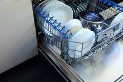 Un lavaplatos para los platos y los cubiertos ahorra tiempo y el dinero y el lavaplatos ahora es un placer y no una obligación Fotos de archivo