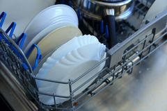 Un lavaplatos para los platos y los cubiertos ahorra tiempo y el dinero y el lavaplatos ahora es un placer y no una obligación Imagenes de archivo