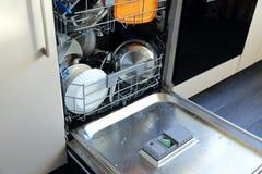 Un lavaplatos para los platos y los cubiertos ahorra tiempo y el dinero y el lavaplatos ahora es un placer y no una obligación Fotografía de archivo libre de regalías