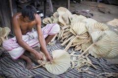 Un lavoratore è occupato nella fabbricazione del fan tenuto in mano Fotografie Stock Libere da Diritti