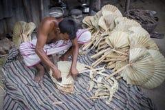 Un lavoratore è occupato nella fabbricazione del fan tenuto in mano Immagine Stock