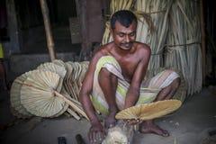 Un lavoratore è occupato nella fabbricazione del fan tenuto in mano Immagine Stock Libera da Diritti