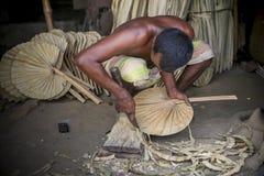 Un lavoratore è occupato nella fabbricazione del fan tenuto in mano Immagini Stock