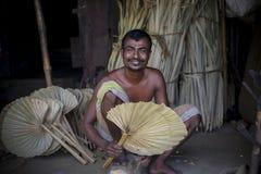 Un lavoratore è occupato nella fabbricazione del fan tenuto in mano Fotografia Stock Libera da Diritti