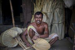 Un lavoratore è occupato nella fabbricazione del fan tenuto in mano Fotografia Stock