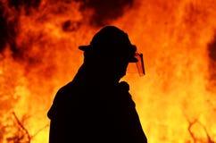 Un lavoratore addetto al salvataggio del pompiere alla fiammata di incendio di arbusti Fotografia Stock Libera da Diritti