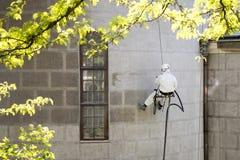 Un lavoratore che indossa un ingranaggio protettivo che pulisce una facciata di pietra fotografia stock libera da diritti