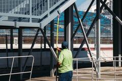 Un lavoratore con una pittura con un rullo dipinge un ponte pedonale immagini stock libere da diritti