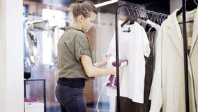 Un lavoratore della ragazza in un negozio di vestiti sta cocendo a vapore i vestiti fotografia stock libera da diritti