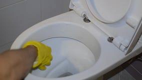 Un lavoratore domestico pulisce la toilette nella toilette facendo uso dei prodotti chimici di famiglia in guanti gialli video d archivio