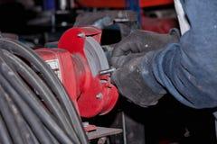Un lavoratore indossa un pezzo di ferro con la smerigliatrice fotografia stock libera da diritti