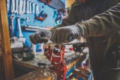 Un lavoratore maschio in un'officina di servizio dello sci ripara il piano di scorrimento degli sci Primo piano di una mano con u immagine stock