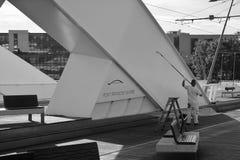 Un lavoratore ridipinge un ponte immagine stock