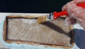 Un lavoratore sta applicando la resina per la riparazione del foro immagini stock