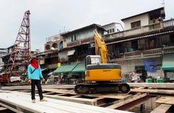 Un lavoratore sta vicino ad un escavatore Immagine Stock