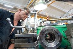 Un lavoratore, un uomo in una camicia nera ed occhiali di protezione, comandi una macchina meccanica Lavoro di giro nella produzi fotografia stock libera da diritti