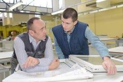Un lavoro attento di due operai alla fabbrica delle finestre del PVC immagini stock libere da diritti