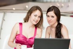Un lavoro delle due ragazze su un computer portatile Immagine Stock
