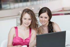 Un lavoro delle due ragazze su un computer portatile Fotografia Stock Libera da Diritti