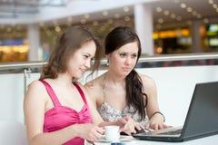 Un lavoro delle due ragazze su un computer portatile Fotografie Stock Libere da Diritti