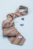 Un lazo en el fondo azul adornado con los pequeños corazones Imagen de archivo libre de regalías
