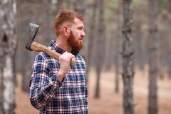 Un leñador con el pelo del jengibre y beardstands en el bosque y los controles un hacha y miradas en alguna parte outdoors imágenes de archivo libres de regalías