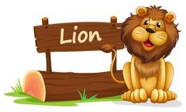 Un león cerca de una señalización de madera Foto de archivo