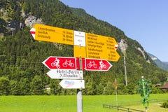 Un letrero en Wengen que indica tiempo que viaja a otros pueblos alpinos suizos imagen de archivo