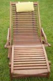Un lettino di legno su erba verde fotografia stock