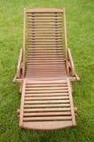 Un lettino di legno su erba verde fotografie stock libere da diritti