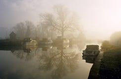 Un lever de soleil brumeux sur le fleuve Images stock