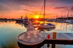 Un lever de soleil majestueux avec le bateau se reposant près du dock comme foregrou photo stock