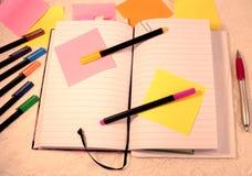 Un libro abierto del diario, notas pegajosas y plumas del fieltro en colores del varius imagen de archivo
