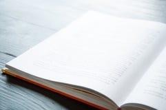 Un libro abierto está en el tableAn que el libro abierto está en la tabla Punto negro fotos de archivo
